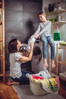 Mãe e filha colocando as roupas em uma máquina de lavar