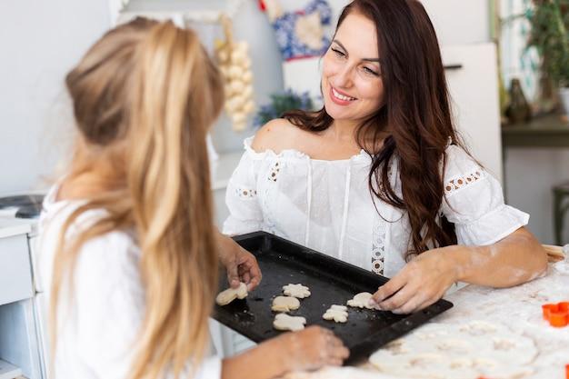 Mãe e filha colocando massa na bandeja