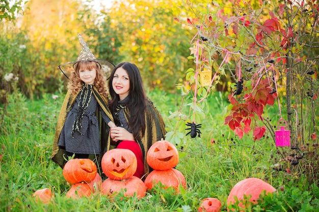 Mãe e filha com abóboras vestidas de bruxas ao ar livre
