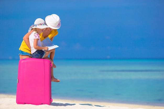 Mãe e filha com bagagem e mapa na praia