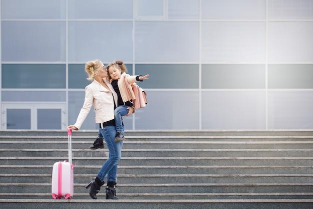 Mãe e filha com bagagem rosa na jaqueta rosa contra o aeroporto.