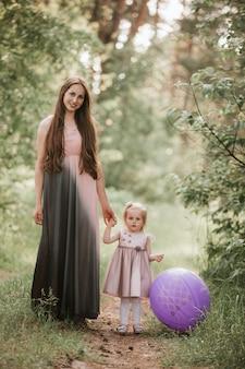 Mãe e filha com balões. linda mãe feliz com a filha se divertindo no campo verde segurando balões.