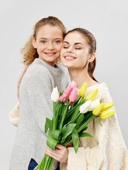 Mãe e filha com buquê de flores, conceito de dia das mães