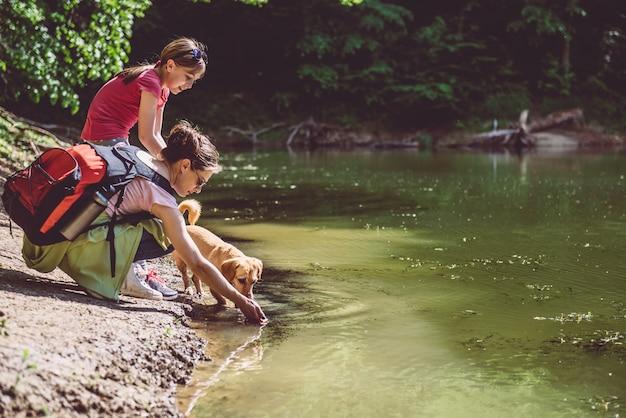 Mãe e filha com cachorro à beira do lago