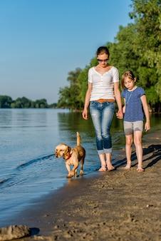 Mãe e filha com cachorro andando pelo rio