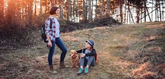 Mãe e filha com cachorro na floresta durante o pôr do sol