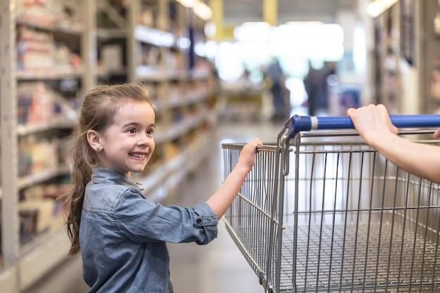 Mãe e filha com camisas azuis fazendo compras no supermercado usando o carrinho