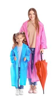 Mãe e filha com guarda-chuva no fundo branco