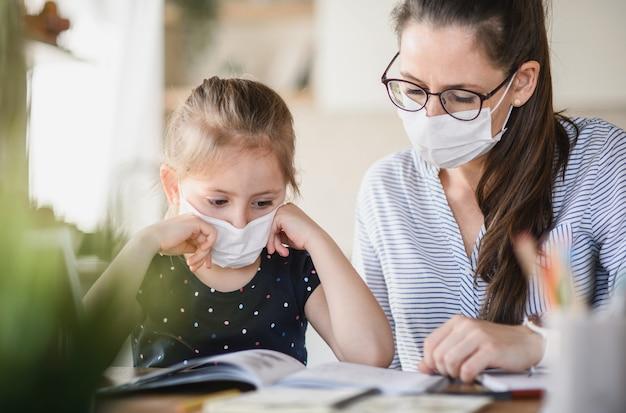 Mãe e filha com máscaras, aprendendo dentro de casa em casa, o conceito de vírus corona e quarentena.