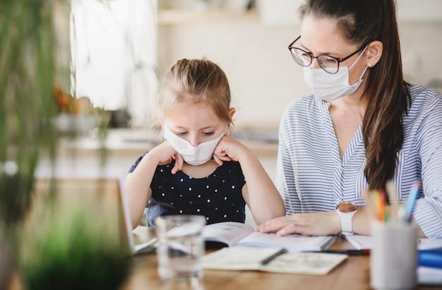 Mãe e filha com máscaras, aprendendo dentro de casa em casa, o vírus corona e o conceito de quarentena.