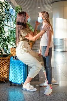 Mãe e filha com máscaras médicas no aeroporto. proteção contra coronavírus