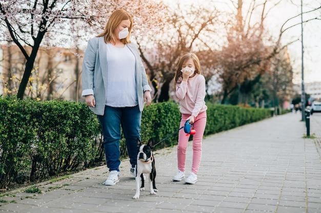 Mãe e filha com máscaras protetoras em seus rostos, desfrutando de um passeio no parque com seu cachorro.