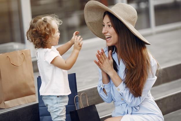 Mãe e filha com sacola de compras em uma cidade