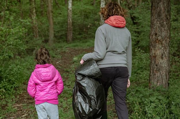 Mãe e filha com sacos de lixo limpam o meio ambiente do lixo.