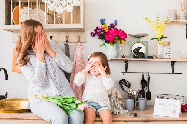 Mãe e filha com tulipas cobrindo os olhos