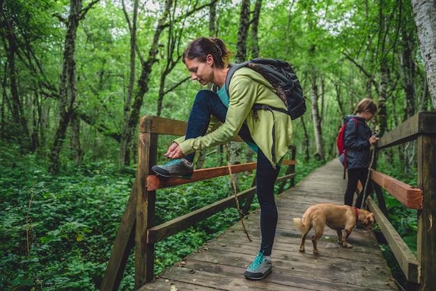 Mãe e filha com um cachorro, caminhadas na floresta
