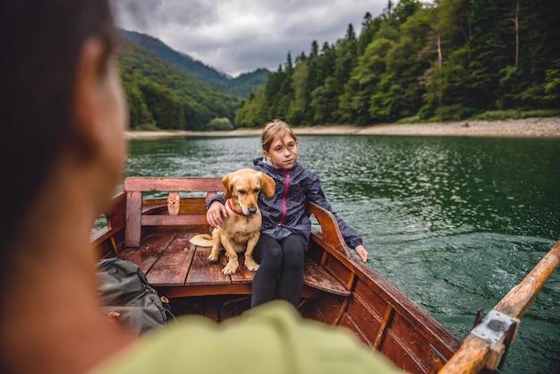 Mãe e filha com um cachorro remando um barco