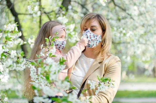 Mãe e filha com uma máscara no rosto estão na cidade ao ar livre