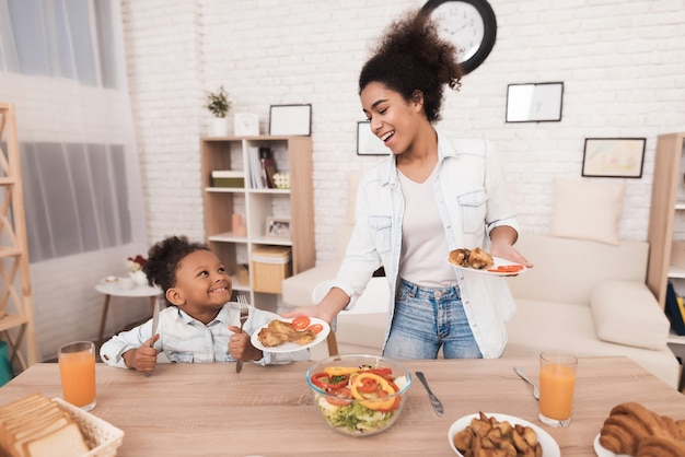 Mãe e filha comem juntos na cozinha.