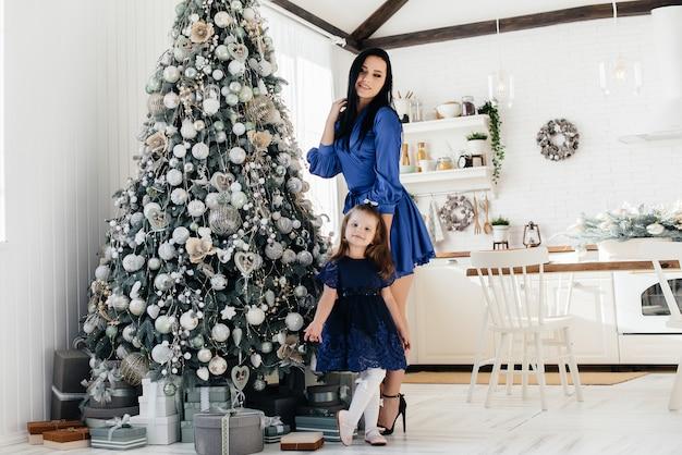Mãe e filha comemoram e brincam perto da árvore de natal no natal. feriado.