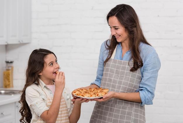 Mãe e filha comendo alguns deliciosos bolos