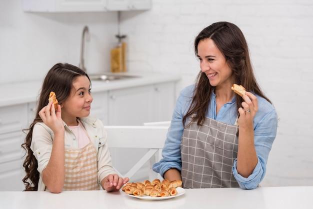 Mãe e filha comendo alguns doces na cozinha