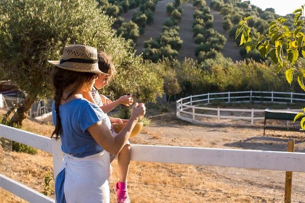 Mãe e filha comendo azeitonas colhidas no campo