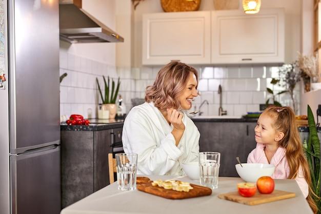 Mãe e filha comendo frutas e mingau. nutrição saudável para crianças, refeição matinal. família caucasiana tomando café da manhã em uma cozinha moderna e leve