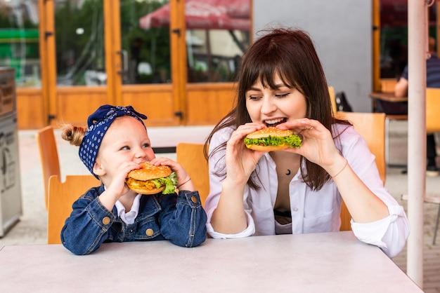 Mãe e filha comendo hambúrgueres saborosos em um café de fast food
