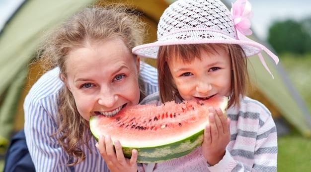 Mãe e filha comendo melancia perto de uma barraca no prado ou parque. família feliz no piquenique no camping.