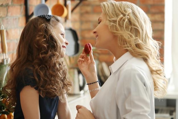 Mãe e filha comendo morangos na cozinha