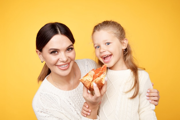 Mãe e filha comendo pizza juntos e se divertindo isolados na sala amarela.