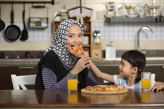 Mãe e filha comendo pizza