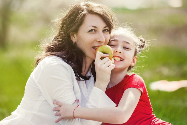 Mãe e filha comendo uma maçã na natureza