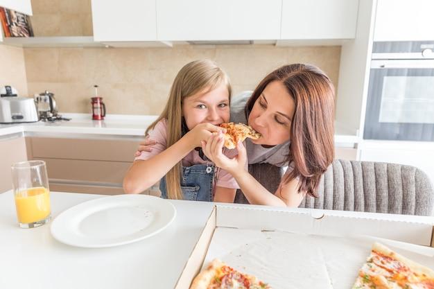 Mãe e filha comendo uma pizza saborosa