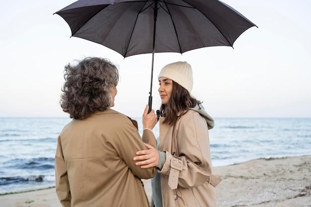 Mãe e filha compartilhando um momento de ternura na praia sob um guarda-sol
