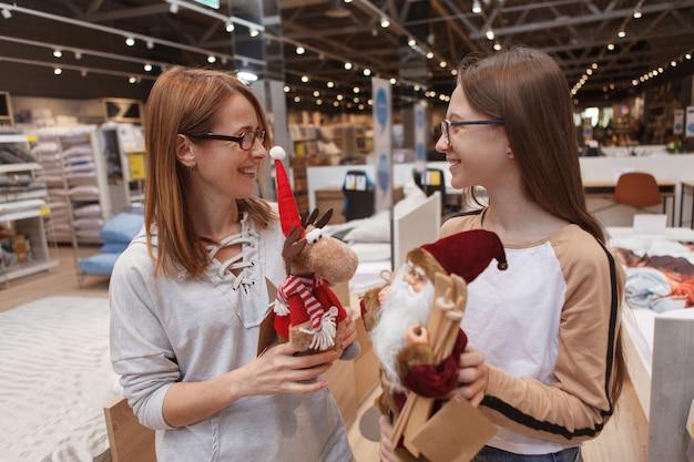 Mãe e filha comprando decorações de natal em uma loja de móveis