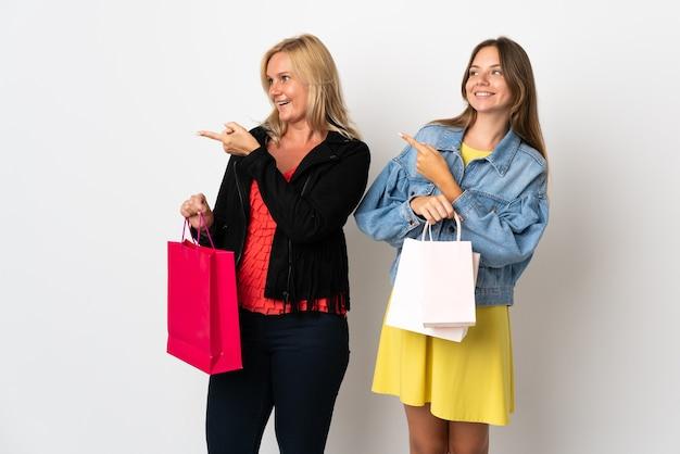 Mãe e filha comprando roupas apontando o dedo para o lado na lateral