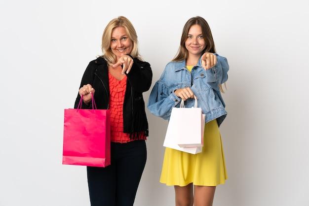 Mãe e filha comprando roupas isoladas na parede branca apontam o dedo para você com uma expressão confiante