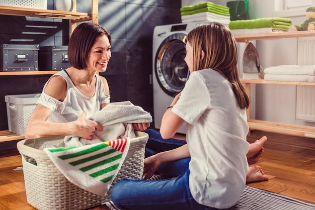 Mãe e filha conversando e classificando a roupa no chão