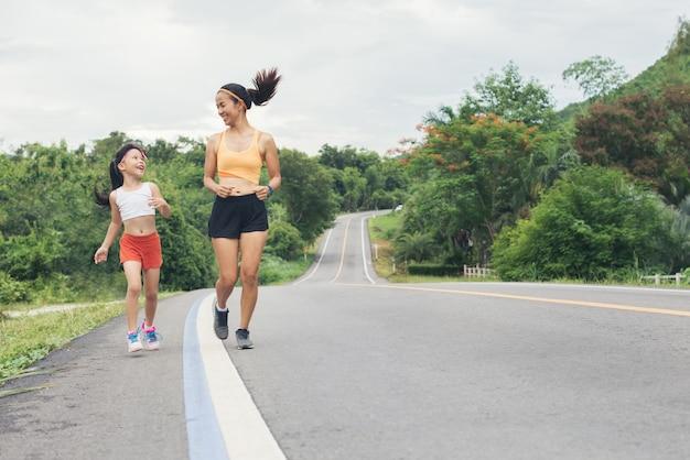 Mãe e filha correndo correndo ao ar livre