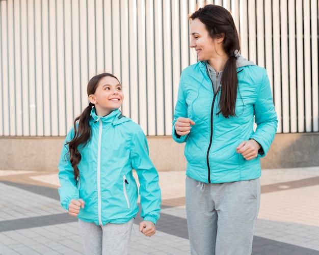 Mãe e filha correndo juntos