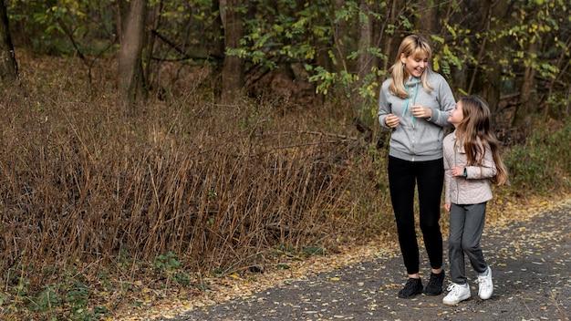 Mãe e filha correndo na natureza