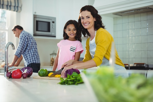 Mãe e filha cortar legumes na cozinha