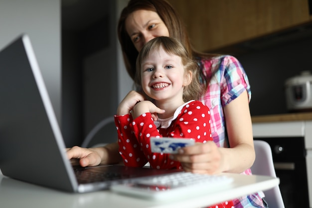Mãe e filha cozinha digitar detalhes do cartão de crédito