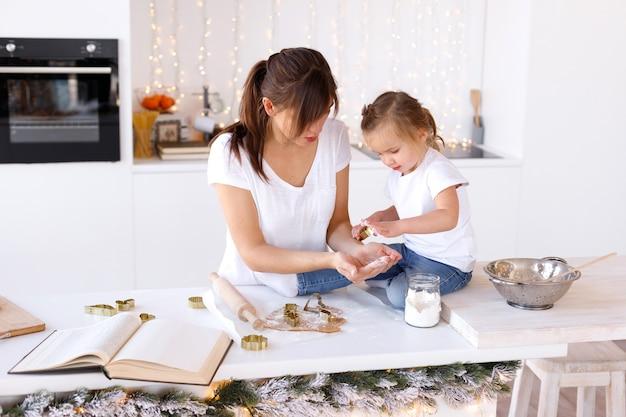 Mãe e filha cozinham biscoitos no natal