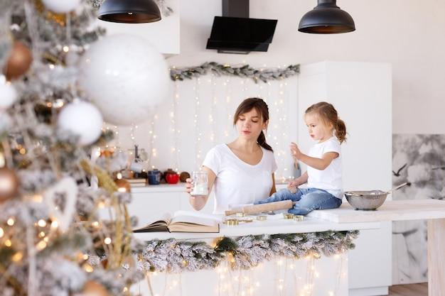Mãe e filha cozinham em casa no natal na cozinha