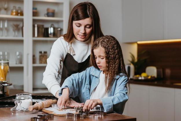 Mãe e filha cozinhando em casa