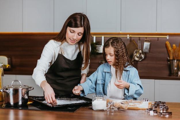 Mãe e filha cozinhando juntas em casa