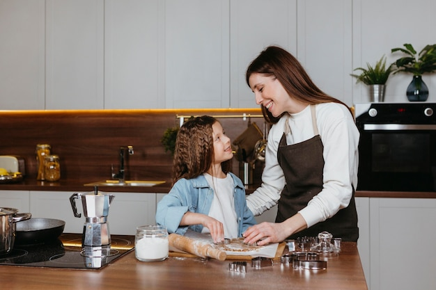 Mãe e filha cozinhando juntas na cozinha de casa